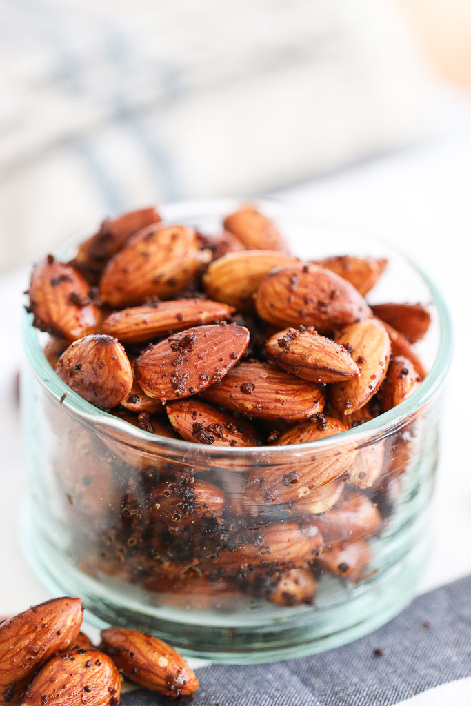 this is a close up shot of homemade roasted spiced almonds glistening with their coating, and sitting in a clear glass bowl