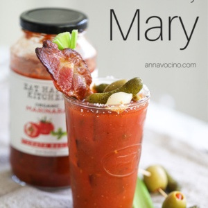 this is a PIN for Pinterest of the the bacon Bloody Mary with celery and bacon garnished glass of bloody Mary cocktail with a jar of Eat Happy Marinara behind it
